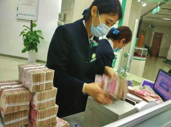 银行工作人员正在清点成捆的钞票