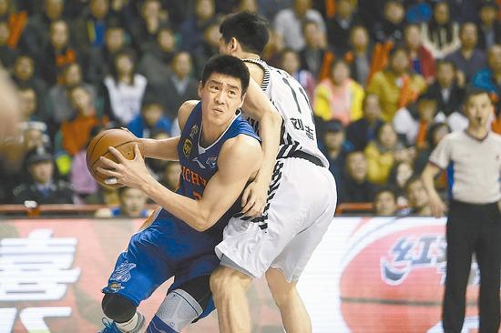 四川队球员张春军(左)在比赛中上篮。