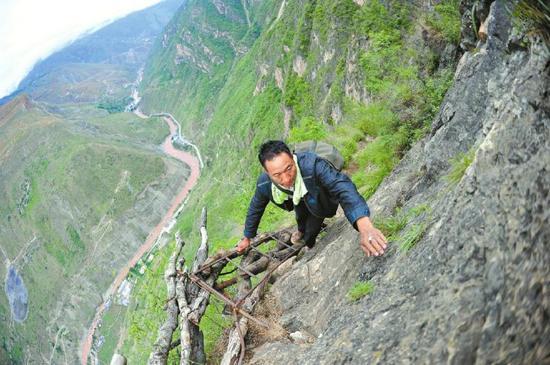 26日,一位村民爬天梯上山,身后陡峭的悬崖让人心惊肉跳。