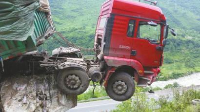 货车车头冲出坡道将近2米多,悬吊在外。