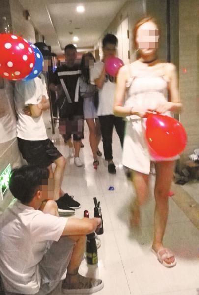 """小贩蹲在写字楼楼道里贩卖""""气球"""",而来来往往的年轻人都喜欢""""吹气球""""。"""