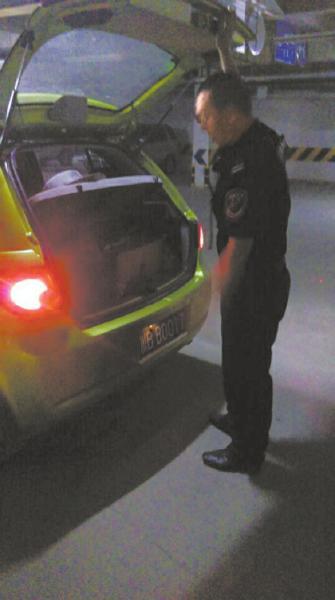 保安正在检查陈先生车的后备厢