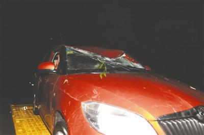 小车被打捞上岸,车身前部、顶部受损,后保险杠脱落