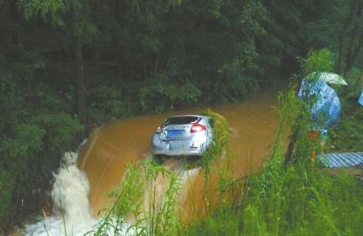 洪雅县一辆轿车停在路边被冲进水沟。