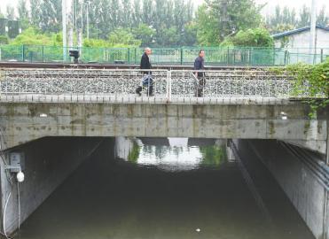 被淹的涵洞内,积水有膝盖深,通行不便的市民们无奈翻过桥上的防护栏横穿铁路。