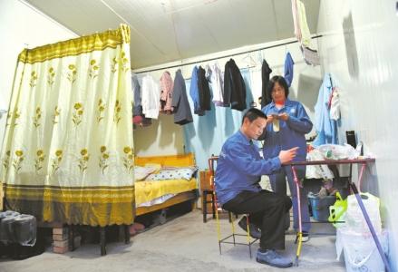 袁志全夫妇住在距离炸药库70米的板房里,下班的闲暇时间,袁志全用手机看小说,妻子在一旁纳鞋垫。
