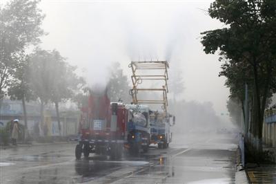 昨日,多功能抑尘车和雾炮车在双流一工地外喷雾除霾 摄影记者 张建