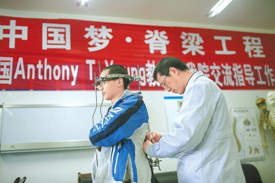 梁益建正在给患者调整治疗器。