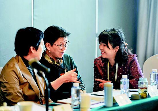 ◆通过手语翻译,高晓笛委员(中)正在和其他委员交流。