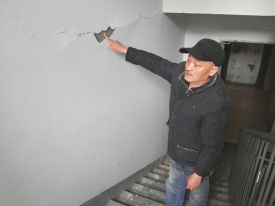 业主刘先生指着墙面水泥面脱落处。