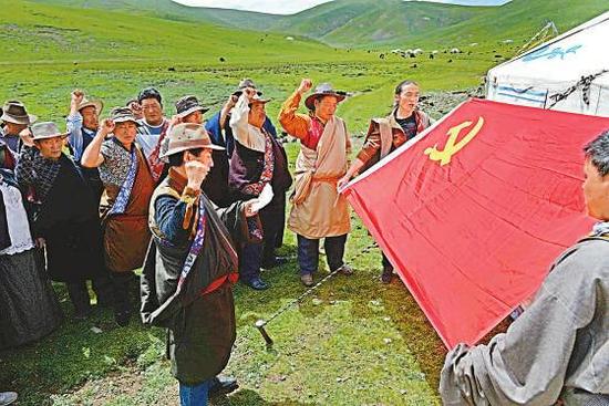 在石渠县海拔4500米处的尼呷镇城关四村远牧点,该村党支部组织党员在党旗前重温入党誓词。 本报记者 李向雨 摄(资料照片)