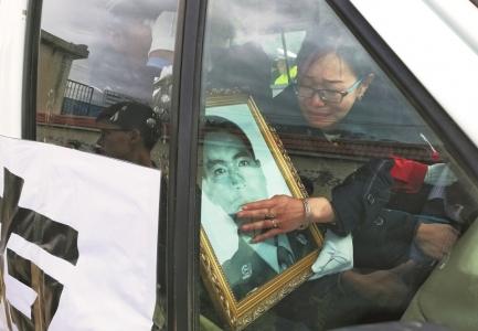 妻子杨茜将丈夫遗像搂在怀里,含泪送丈夫回家。