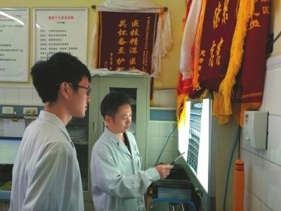 8月2日,魏国医生(右)正在给科室的新同事传授经验。
