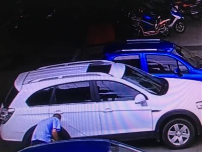 视频监控画面显示,蓝色工装男子对着车轮放气。