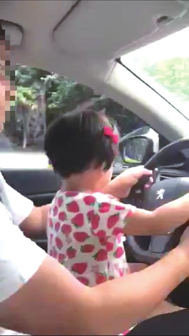 男子抱女儿开车的画面