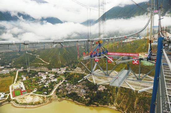 9月26日,四川省泸定县,雅康高速兴康特大桥首节钢桁梁吊装,工人在高空施工。杨涛摄