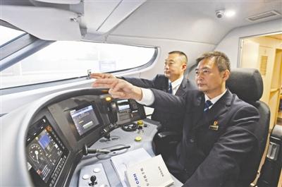 11月6日,西成高铁首发司机杜辉(右)和唐建,正在检测升级后的信号系统,并熟悉各种信号场景