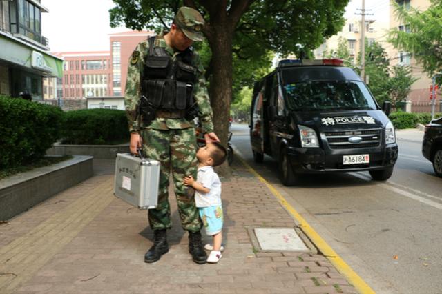 两岁儿子路遇执勤武警爸爸求抱抱 紧抱裤腿不放手
