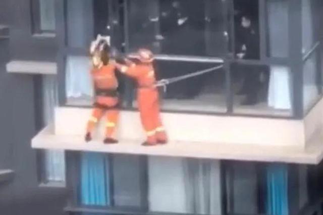 女子坐在17楼窗户外沿欲轻生 消防员一把抱住拉回