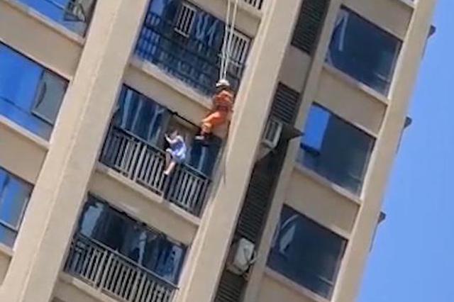 女子坐17楼窗台护栏欲跳楼 消防员从18楼跃下将其解救
