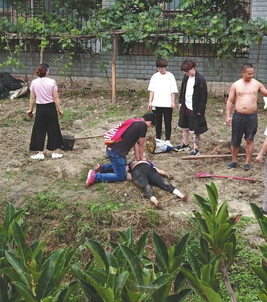 老人被救起后,廖圳龙跪地实施心肺复苏。
