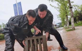 民警蹲在60厘米深水掀井盖排险