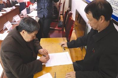 村民大会上,村民签订不大操大办酒席的?#20449;?#20070;(图右为赵纯良)