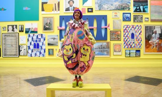 展览策展人、当代艺术家格雷森•佩里(Grayson Perry)在夏季展作品前。