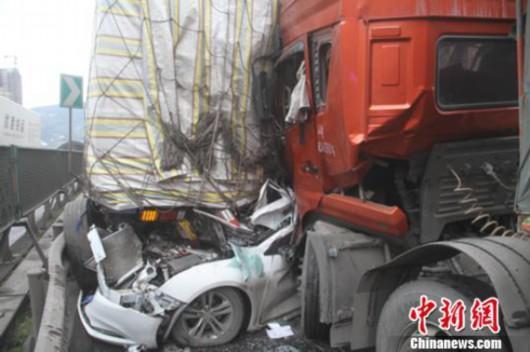 图片说明:大货车之间被挤变形的小车。廖涛 摄