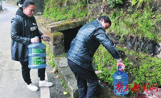 市民在桂花路靠西河南路隧道处山体上取山泉水饮用