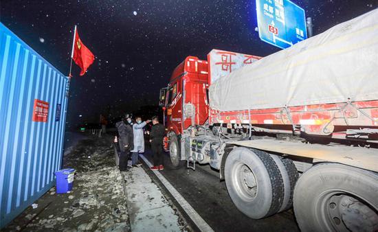 2月8日,姜睿锟正在孟获城疫情防控卡点,为司机测量体温