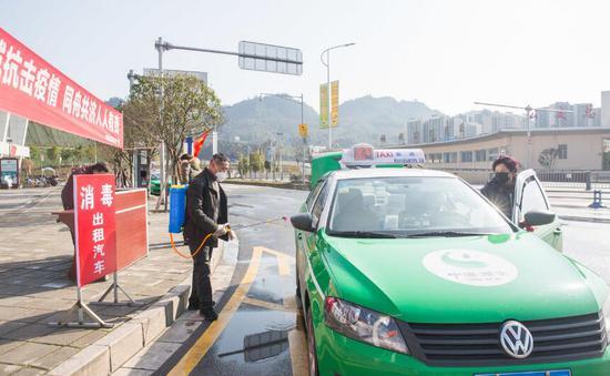 雅安汽车客运站外,工作人员对出租车进行消毒