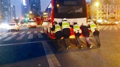 9日傍晚,牛王庙路口,交警三分局辅警们合力将熄火公交车推过路口 图据网友
