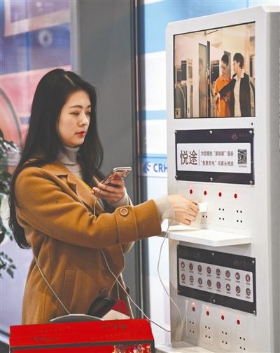 阳知涵在车站候车厅给手机充电