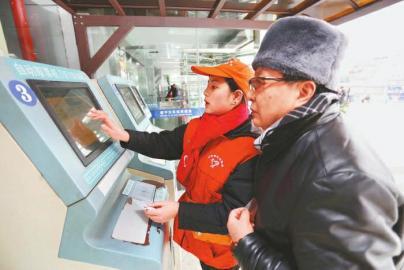 春运期间,遂宁多部门出动,全力保障旅客出行。图为志愿者为旅客取票。 刘昌松 摄(视觉四川)