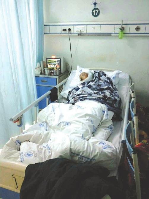 躺在病床上的周仕贵。