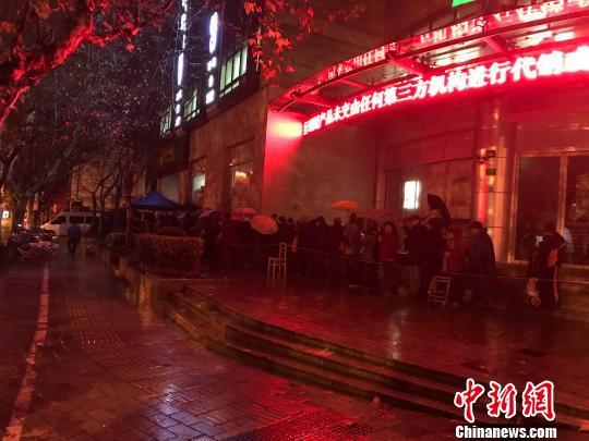 1月5日清晨5点半,在上海静安邮政支局,市民冒着寒风与冷雨,撑伞排队,抢购首发的戊戌狗年生肖邮票。 郭容 摄