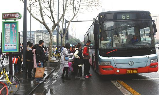 正在成都红星路广场南68路公交车站排队上车的乘客。
