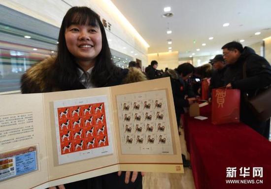 1月5日,工作人员在邮品发售现场展示《戊戌年》特种邮票。新华社记者孙参摄