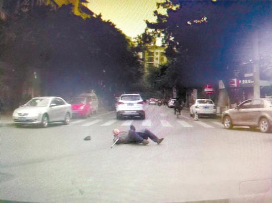 老人摔倒在马路中央。