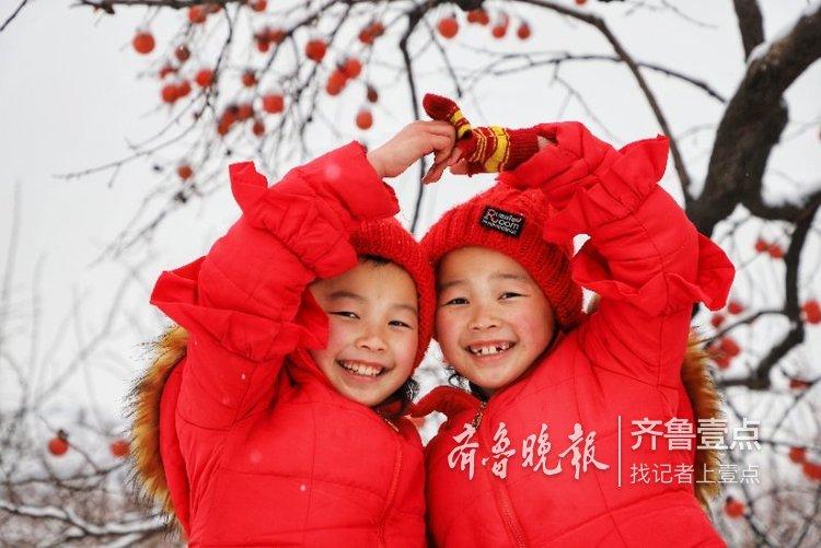 雪打枝头 树下的双胞胎小姐妹玩嗨了