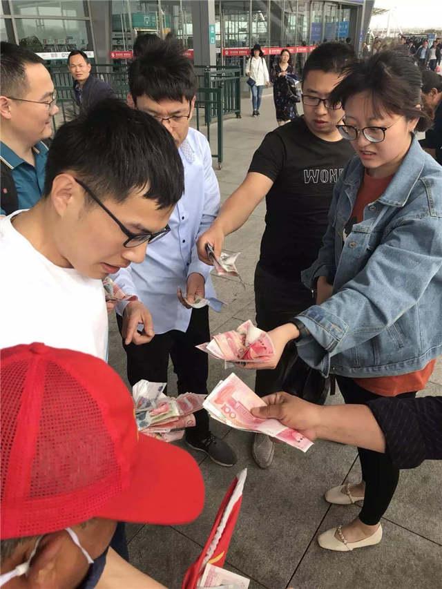 青岛北站乘客万余元钞票被风刮跑 几分钟后钱一分不少回来了