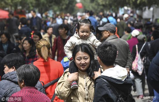 2018年4月14日,济南,一女士肩扛女儿逛庙会。