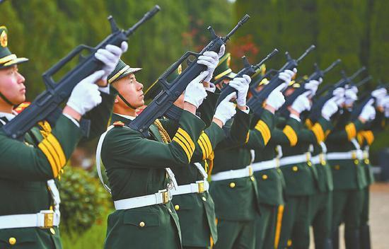 鸣礼枪,为烈士送行。 记者郭尧 摄