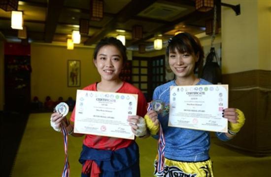 ↑罗丽和葛绿展示奖牌和奖状。