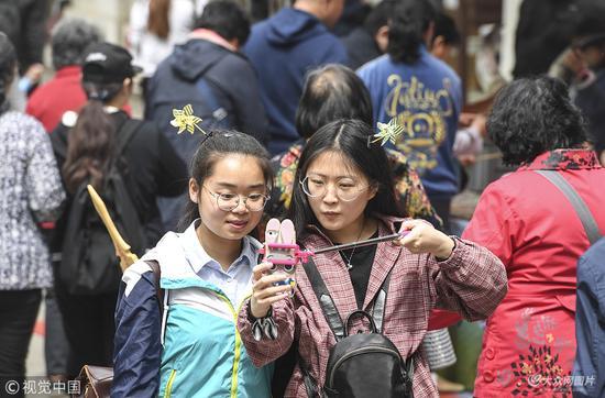 """2018年4月14日,济南,两位女孩头戴""""风车""""头饰在""""人海""""中玩自拍。"""