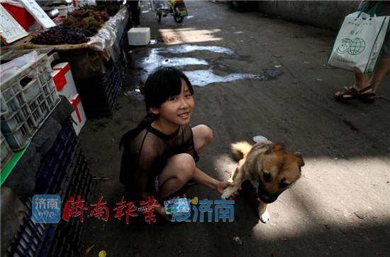 8岁的张子涵把她的小狗也带到市场作伴
