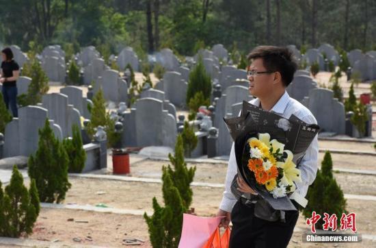 资料图:市民手捧鲜花祭奠亲人。 苏高龙 摄