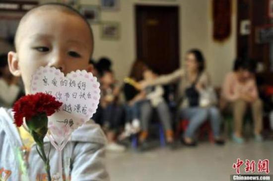 ↑资料图:一名自闭症孩子拿着鲜花与卡片,提前祝妈妈节日快乐。周小云 摄