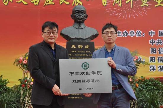 中国戏曲学院院长巴图(左)为阳信县洋湖乡中心小学授牌。